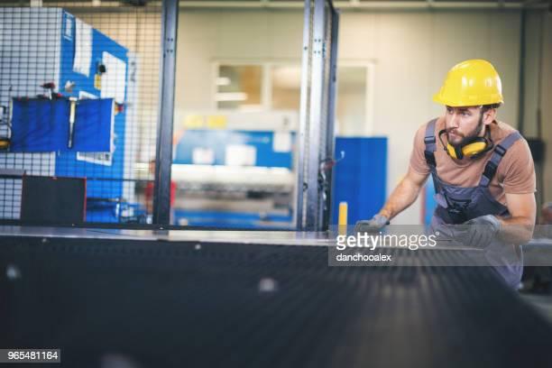 young man processing metal plates in factory - sheet metal stock pictures, royalty-free photos & images