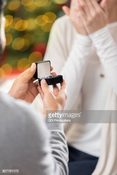 young man proposes to girlfriend during christmastime - engagement ring box stock photos and pictures