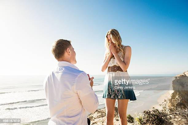 Young man proposing to girlfriend by sea, Torrey Pines, San Diego, California, USA