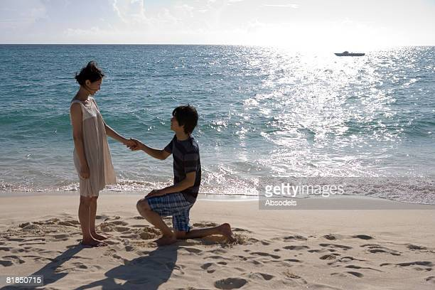 Young man proposing to girlfriend on beach