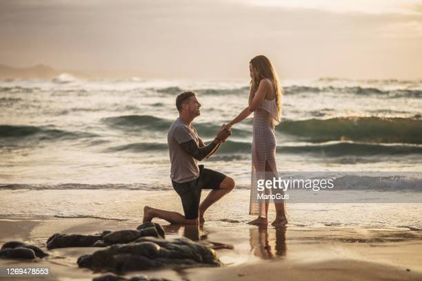 young man proposing to his girlfriend at a beach - engagement stock pictures, royalty-free photos & images