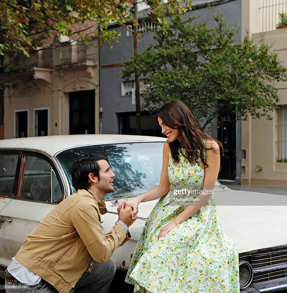Young man proposing to woman against car, smiling : Stock Photo