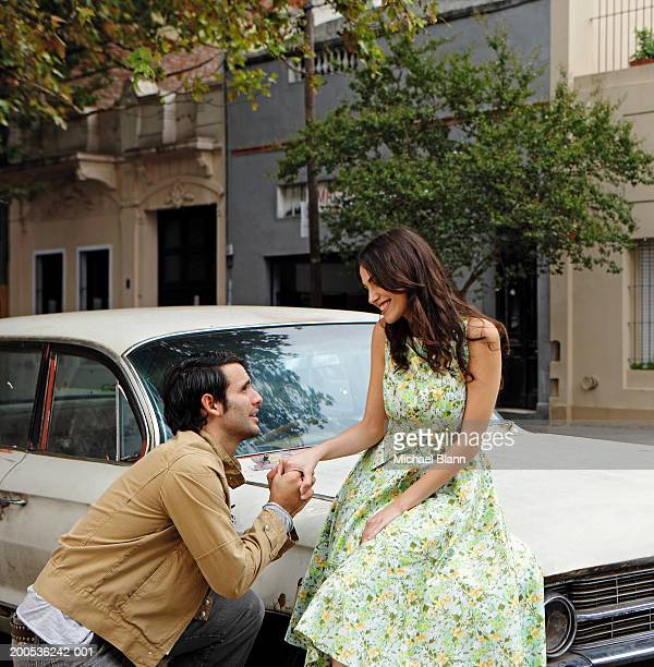 Young man proposing to woman against car, smiling
