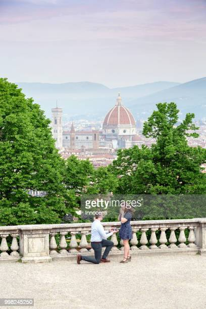 Young man proposing to woman, Santa Maria del Fiore in background, Florence, Toscana, Italy