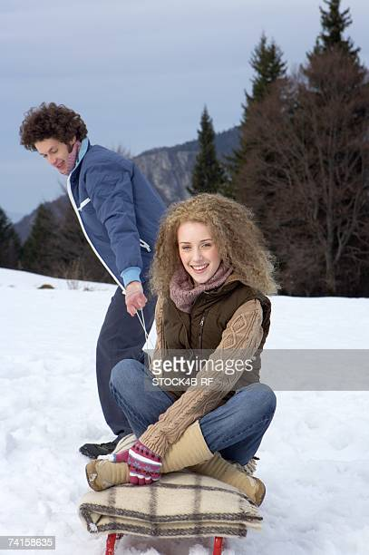 Young man pulling a sled with a blonde woman sitting on it