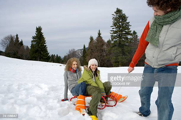 Young man pulling a sled with two women sitting on it