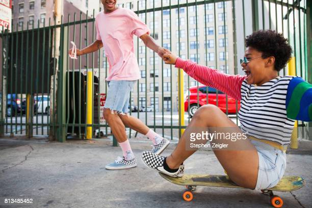 young man pulling a young woman on a skateboard - skating stock pictures, royalty-free photos & images