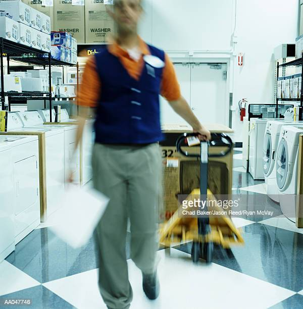 young man pulling dolly in home appliance store (blurred motion) - dolly reed stock photos and pictures