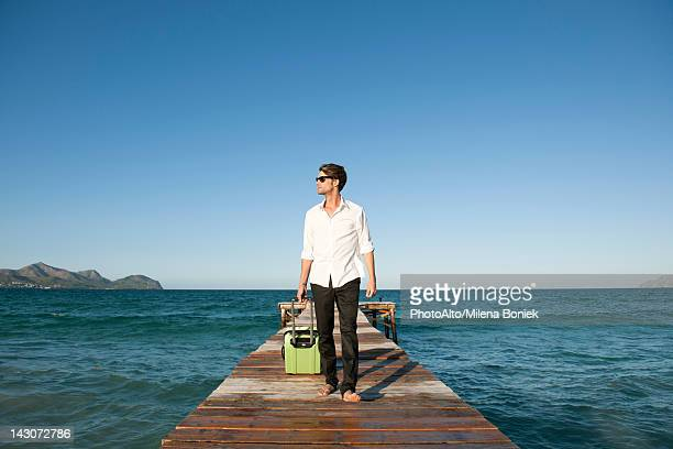 Young man pulling luggage and walking on pier