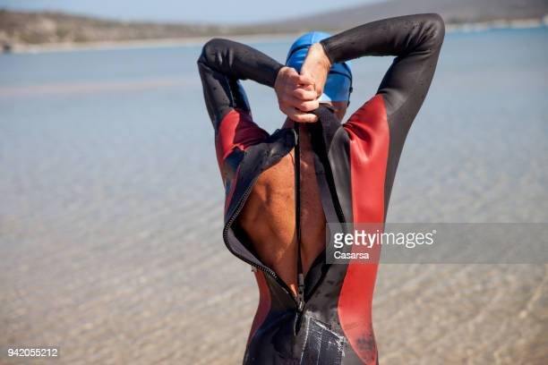 Young man pulling the zipper of a triathlon race suit