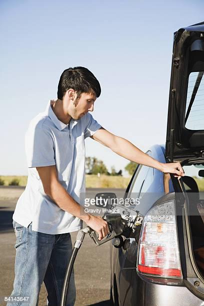 Young man pumping gas