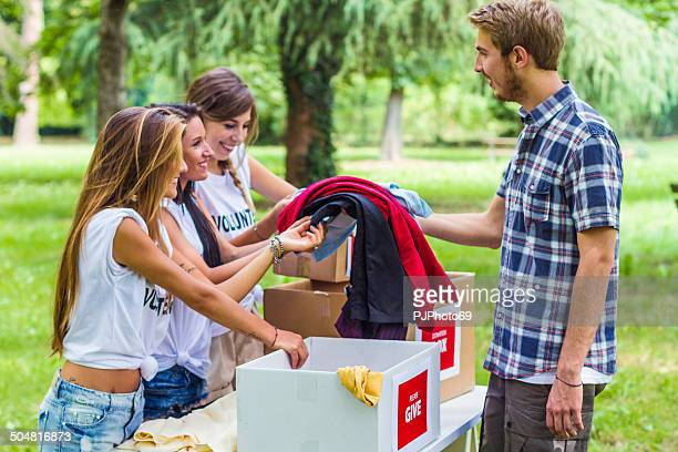 young man purchase clothes from group of volunteers - pjphoto69 stockfoto's en -beelden