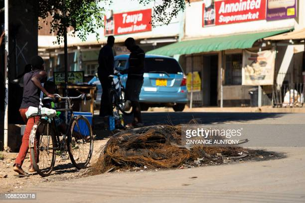 Young man pushes a bicycle past the debris from tyres which were set as barricades at a shopping centre in Rimuka township, Kadoma on January 24,...