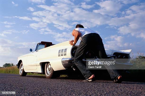 Young Man Pushing Car on Roadside