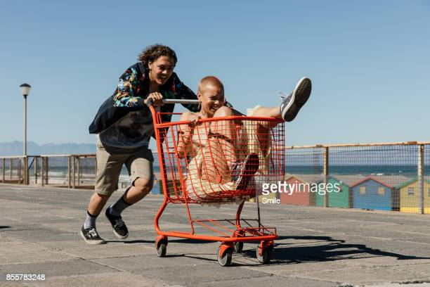 young man pushing girl in red trolley - free stock pictures, royalty-free photos & images
