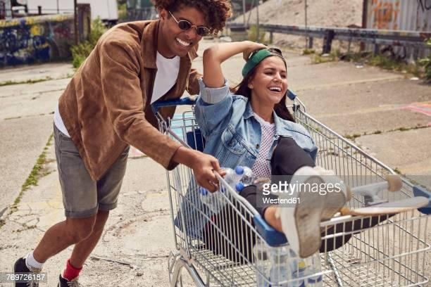 young man pushing girlfriend sitting in shopping cart - respektlosigkeit stock-fotos und bilder