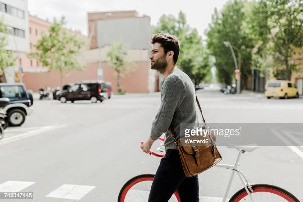 Young man pushing his bike on a street