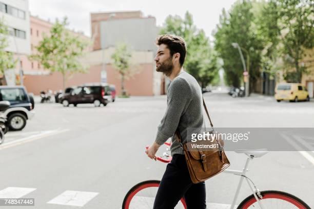 young man pushing his bike on a street - sac porté épaule photos et images de collection