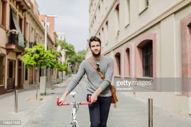Young man pushing his bike