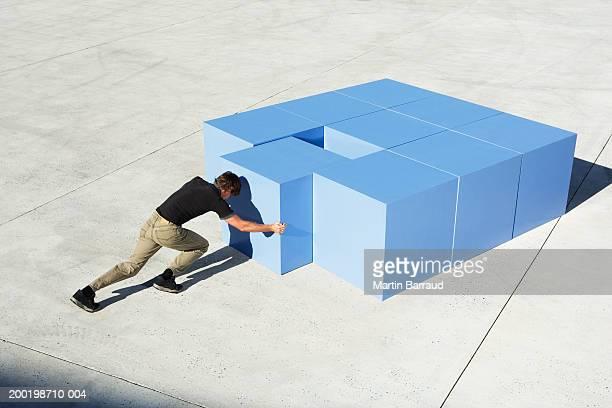 Young man pushing large cube towards arrangement of cubes