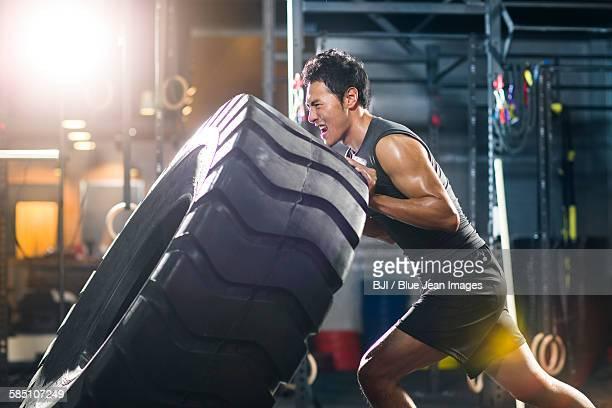 young man pushing large tire in gym gym - só homens jovens imagens e fotografias de stock