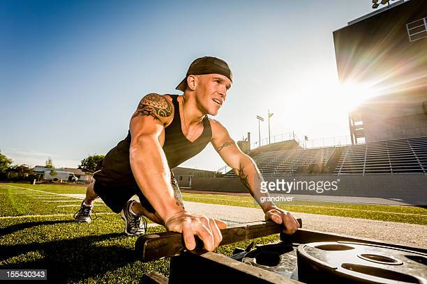 young man pushing weighted sled - pushing stock pictures, royalty-free photos & images