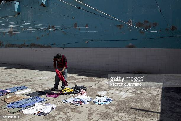 """Young man puts clothes to dry in the yard of """"La Gran Familia"""" shelter, where more than 48 hours ago police rescued 596 people, including 458..."""