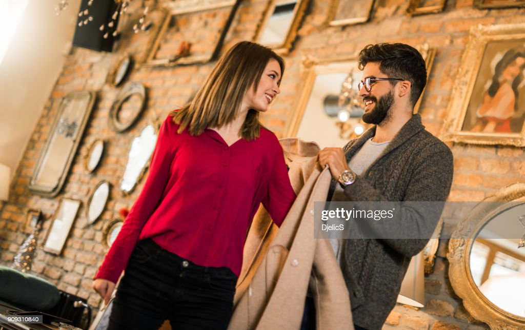 Young man putting a coat on his lady. : Stock Photo
