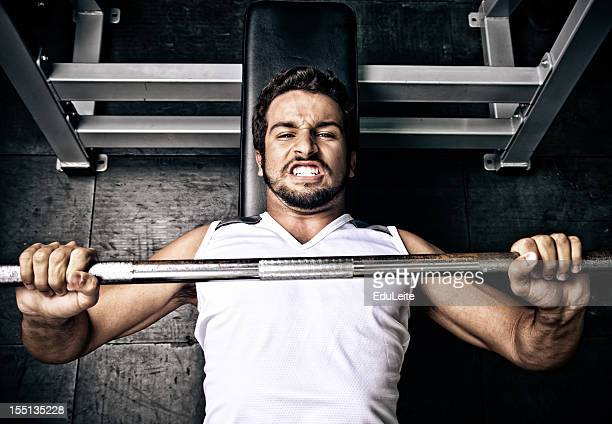 young man putting effort in on a bench press - struggle stock pictures, royalty-free photos & images