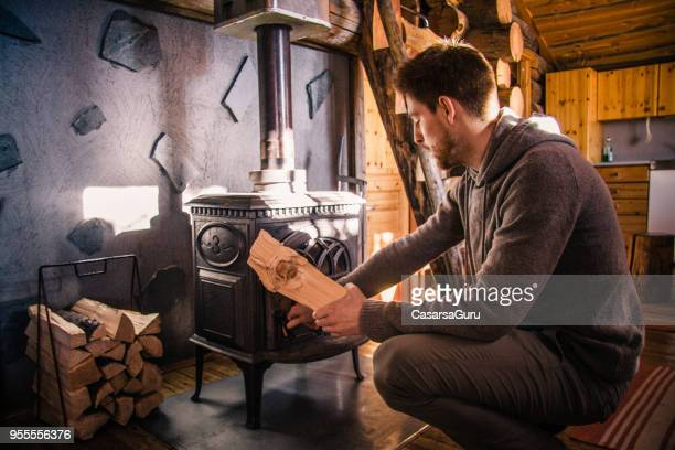 young man putting firewood in wood burning stove - wood burning stove stock photos and pictures