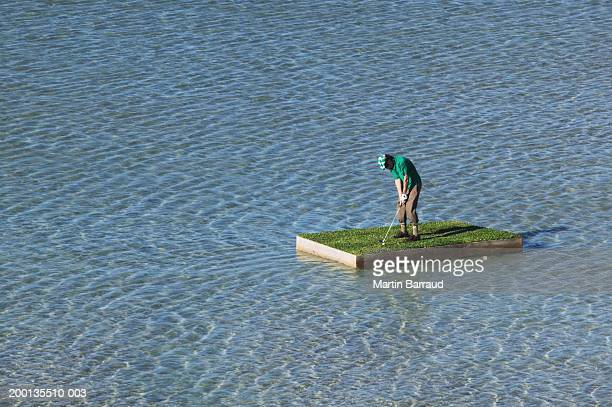Young man putting golf ball on grass topped raft at sea, elevated view