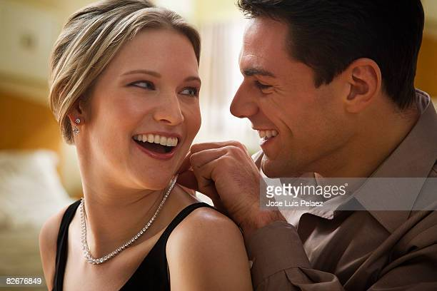 Young man putting necklace on young woman's neck