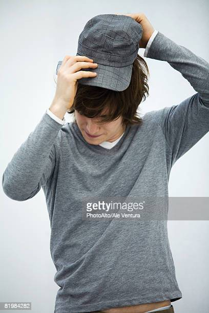 Young man putting on cap, head down, close-up