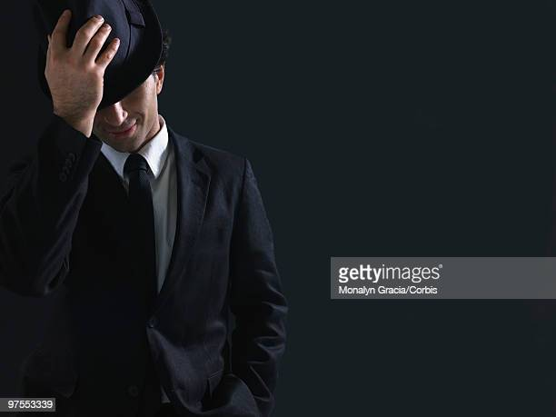 young man putting on fedora - fedora stock pictures, royalty-free photos & images