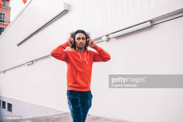 young man putting on headphones walking past concrete wall - hoodie headphones stock pictures, royalty-free photos & images