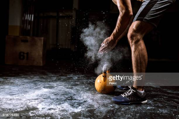 young man putting on sports chalk for lifting barbell - gym stock pictures, royalty-free photos & images