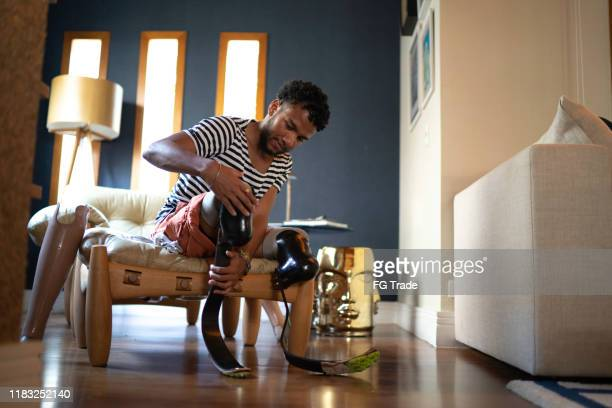 young man putting prosthetic leg at home - sepsis stock pictures, royalty-free photos & images