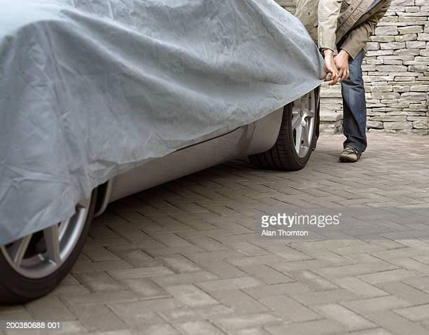 Young man putting protective sheet on car