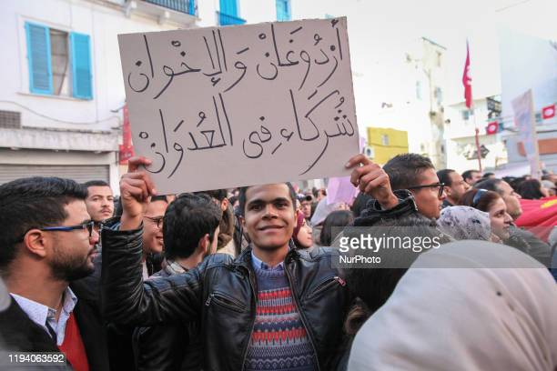 A young man raises a placard which reads 'Erdogan and Muslim Brotherhood are accomplices in the aggression' in protest against the Turkish president...