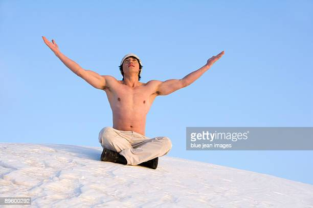 Young man raising his arms while sitting in snow