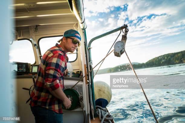 young man raising winch on fishing boat on coast of maine, usa - heshphoto foto e immagini stock