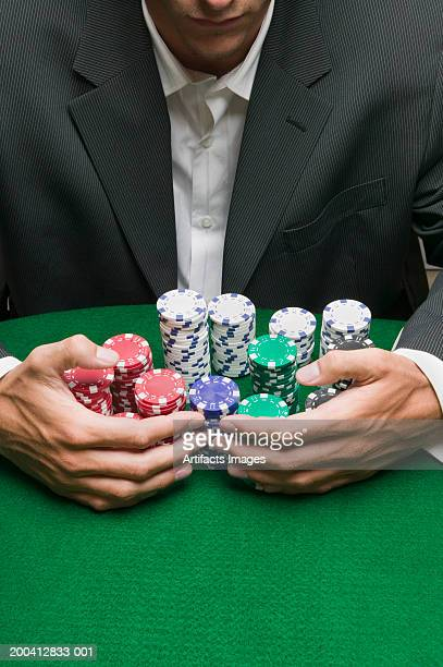 Young man raking in stacks of gaming chips, mid section