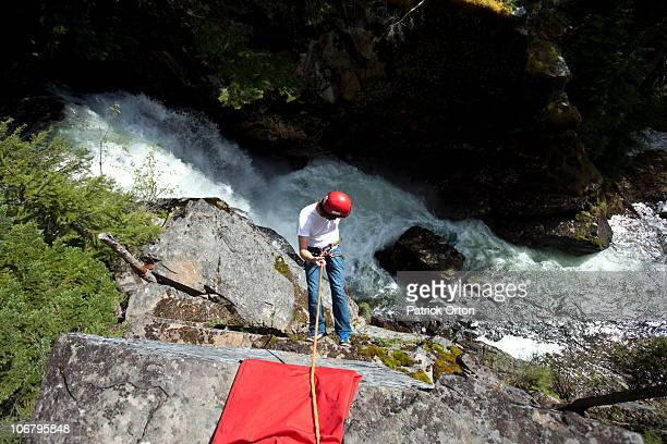 A young man rappels down a cliff next to a waterfall in Idaho.