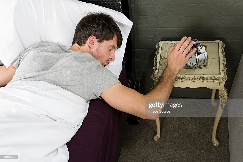 Young man reaching for alarm : Stock Photo