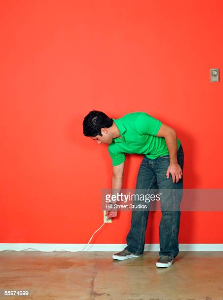 young man reaching for outlet - bending over stock pictures, royalty-free photos & images