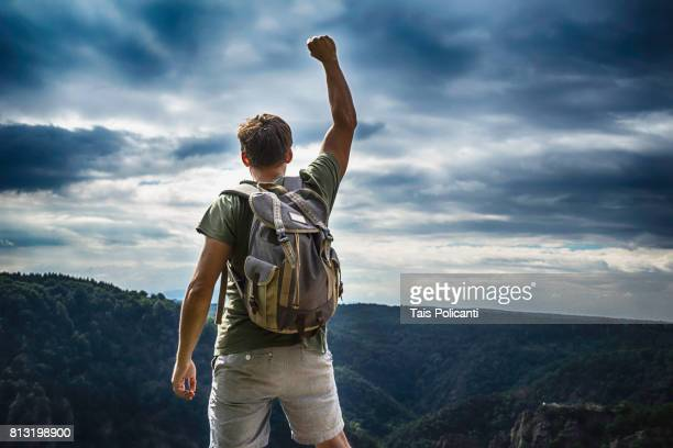 A young man reaching the peak after hiking at the Bodetal valley in Thale - Harz mountains, Thale, Saxony-Anhalt, Germany