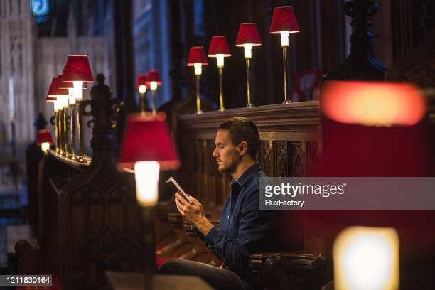 young man reading a bible in the church and praying for coronavirus pandemic around the world - kneeling stock pictures, royalty-free photos & images