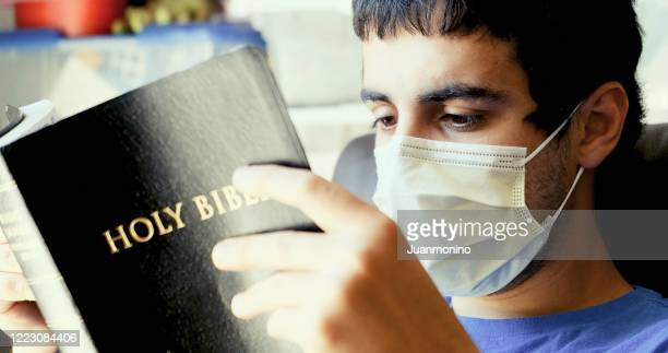 young man reading a bible wearing a surgical mask - prayer book stock pictures, royalty-free photos & images