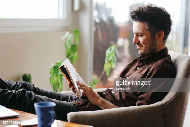 young man reading a book at home - reading stock pictures, royalty-free photos & images