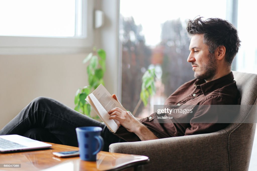 Young man reading a book at home : Stock Photo
